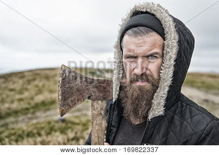 Bearded Handsome Serious Man With Rusty Axe On Mountain Top