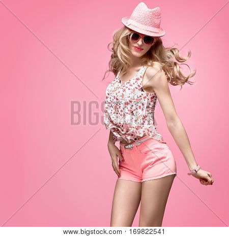 Fashion woman Having Fun Dance. Blond Model Crazy Girl in Stylish Spring Summer Outfit. Fashion Sunglasses, Glamour Pink Shorts, Floral Top.Happy Hipster, Trendy pink fashion Hat.Wavy summer Hairstyle