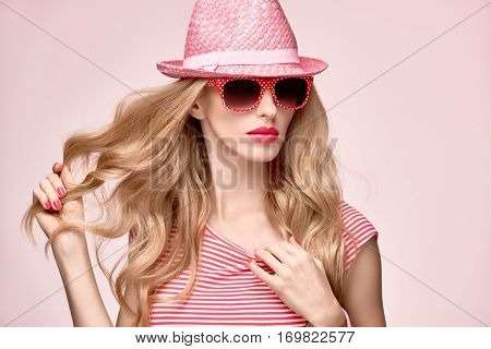 Fashion Model Sexy Girl. Hipster woman Cheeky emotion. Stylish Spring Summer Outfit. Crazy Blond in Fashion Sunglasses, Glamour Pink Shorts, spring Top.Trendy pink fashion Hat.Playful Summer Hairstyle
