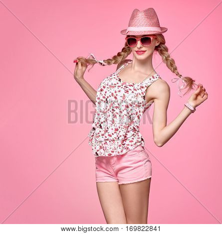 Fashion woman Having Fun. Blond Model Girl in Stylish Spring Summer Outfit Smiling. Fashion Sunglasses, Glamour Pink Shorts, Floral Top.Playful Hipster, Trendy pink fashion Hat, Funny summer Hairstyle