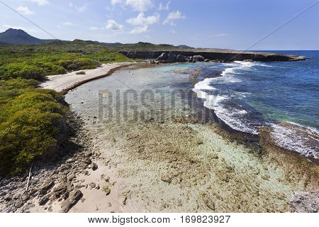 Coastline of Boka Grandi in Christoffel National Park on Curacao with Mount Christoffel on the left side in the distance