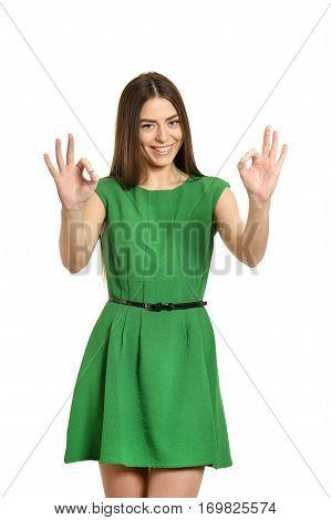 Portrait of woman in green dress doing OK gesture