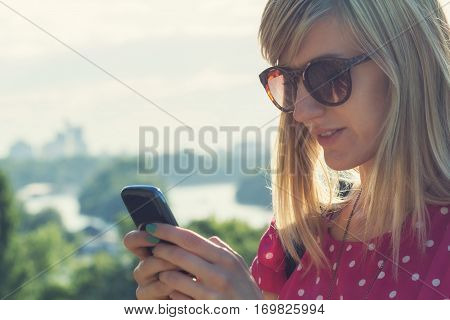 Girl using phone outdoors whit city background.