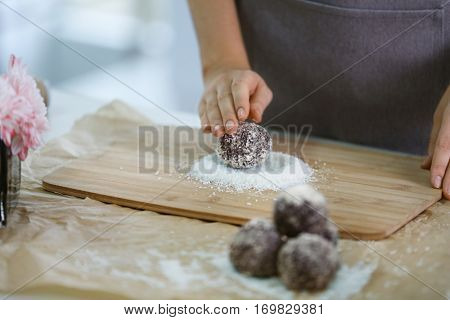 Professional confectioner making tasty chocolate dessert on kitchen table, closeup