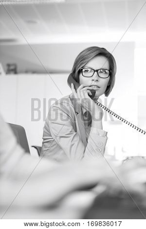 Young businesswoman using telephone in office