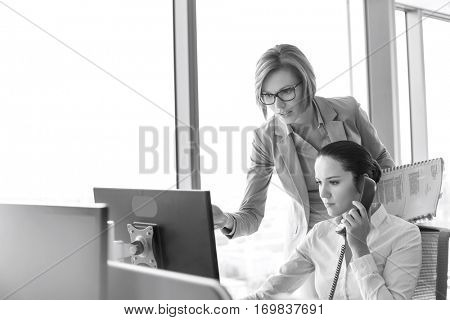 Young businesswoman using landline phone while colleague pointing at computer monitor in office