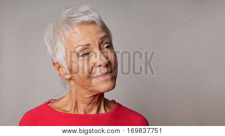 older woman looking pleased at copy space. panoramic 16:9 banner or header format.