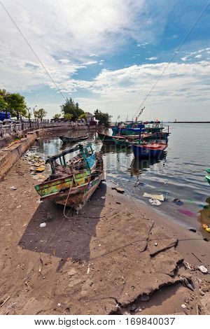 Fishing boats in port. At sand and in water floats a lot of garbage. Phu Quoc island. Vietnam