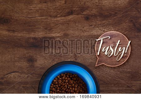 Bowl of dry kibble dog food. Healthy pets feed. Tasty speech bubble. Blue plate on wooden rustic background.