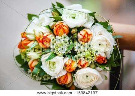 Wedding bouquet with delicate peonies, spring tulips and elegant roses decorated with green plant elements. Bridal bouquet with vintage flowers. Round bunch of fresh flowers. Accessory of bride