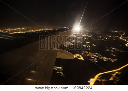 Aerial view of night city landscape. Earth viewed from airplane under aircraft wing. Lights of modern city from the bird fly