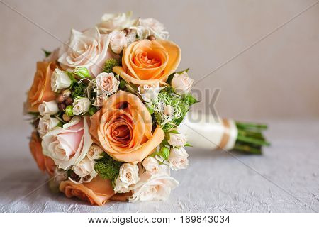 Bridal bouquet with orange and beige roses of different size with handle on white background. Romantic wedding bouquet with beautiful flowers. Elegant round bunch of fresh roses. Accessory of bride