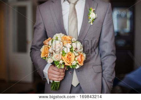 Bridegroom in expensive suit holding bridal bouquet with orange and beige roses of different size with in hands. Elegant buttonhole-flower in jacket. Romantic wedding bouquet, bunch of fresh roses