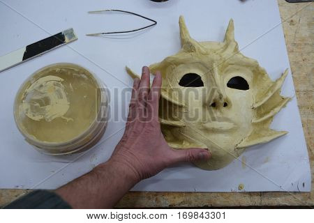 theater demon mask lies on a table on a sheet of paper