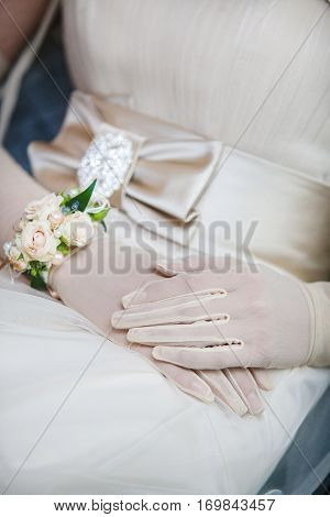 Elegant bridal hands in white gloves with floral decoration focused on wedding dress. Girl in luxury white wedding dress with bangle made of flowers on wrist sitting. Stylish bow on the gown
