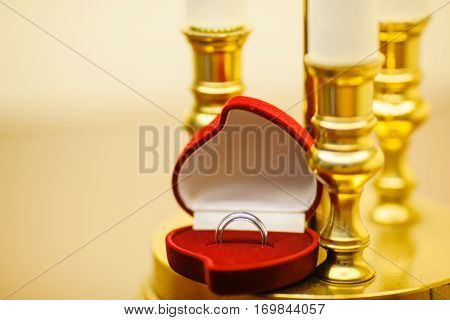 Wedding rings in red heart shape box near candle holders. Female and male platinum rings. Jewelry in container, accessory for wedding day. Symbol of love, two engagement rings. Golden candlesticks
