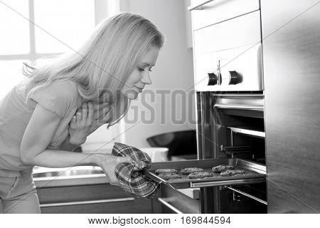 Mid adult woman removing baking tray from oven in kitchen