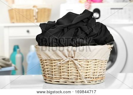Clothes in wicker basket at laundry