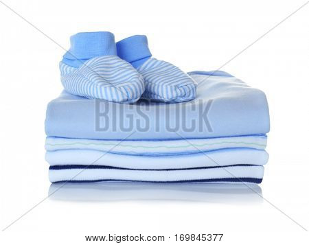 Baby shoes and pile of clothes on white background