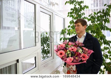 Man with big bouquet of flowers near reception windowin in Maternity hospital