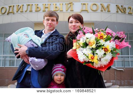 Man with newborn, girl, woman with flowers stand near maternity hospital, text - maternity hospital no. 2