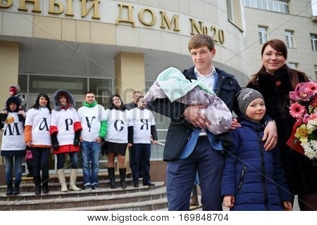 MOSCOW - MAR 22, 2016: Man with newborn, woman, girl and people stand near maternity hospital no. 20, Every year in Moscow, 143000 babies are born, Text translation - maternity hospital, Marusya name