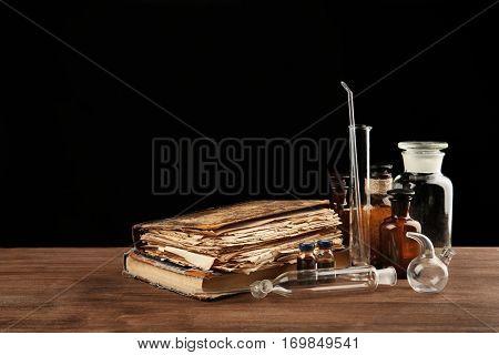 Vintage medicine bottles and books on wooden table