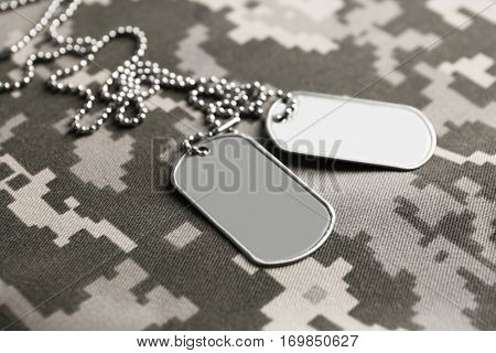 Army tokens on military uniform background