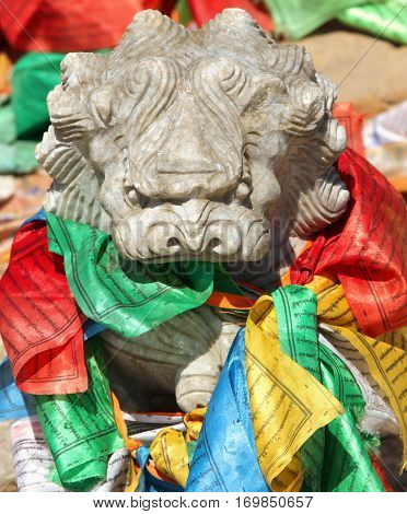 Stone lion figure with traditional buddhist prayer flags in lamasery Inner Mongolia