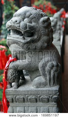 Traditional chinese guardian lion - male leaning his paw upon an embroidered ball (representing supremacy over the world)