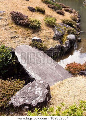 Stone bridge over creek in traditional Japanese landscape garden