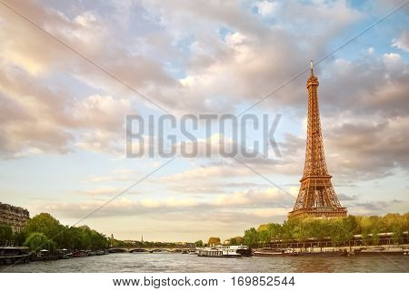The Eiffel Tower and the river Seine at sunset sky background in Paris in the spring