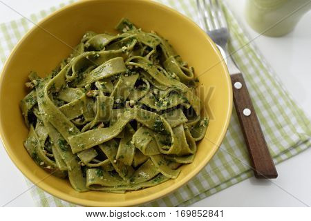 Spinach pasta with pesto sauce in a yellow bowl