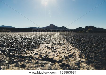 Empty desert road with mountains silhouette on background sunflares from ground shot