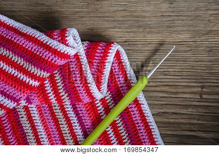 Crocheted Striped Fabric In Red Colors With Crochet Hook On The Old Wood Background