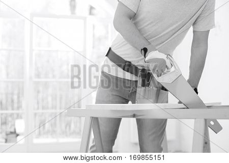 Midsection of man sawing wood in new house