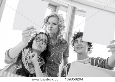 Creative businesspeople analyzing photographs in office