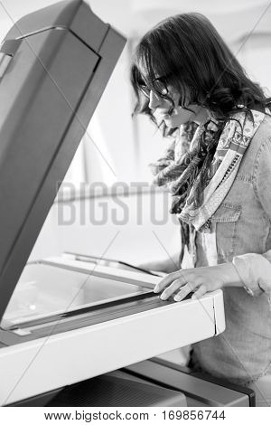 Businesswoman using photocopier in creative office