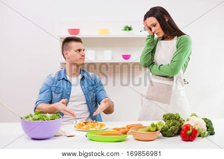Young couple cooking meal in their kitchen.