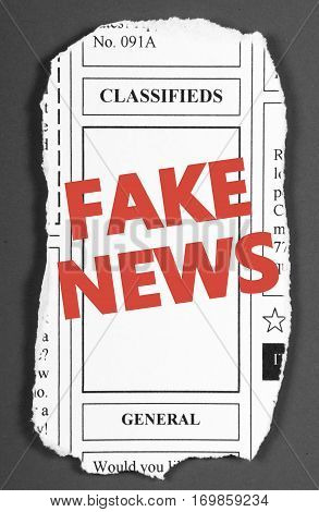 The words Fake News in red text on a white brick wall as a reminder to be aware of hoaxes and disinformation for propaganda uses