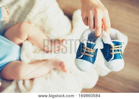 Boots for baby. Mother holding shoes her little boy.
