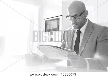 Mid adult businessman having coffee while reading newspaper at home