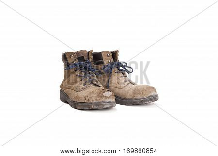 pair of battered old worker boots isolated on white background