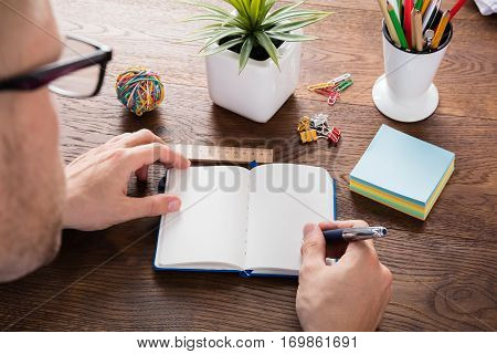 High Angle View Of A Person Writing Note In Blank Diary On Wooden Desk
