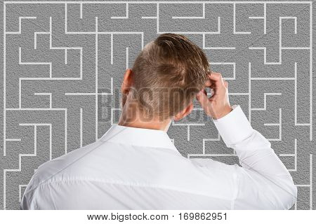 Confused Young Businessman Looking At Labyrinth Trying To Solve Business Puzzle