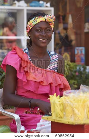 CARTAGENA DE INDIAS, COLOMBIA - JANUARY 23, 2017: Woman in traditional clothing selling fruit in the historic walled city of Cartagena de Indias in Colombia.