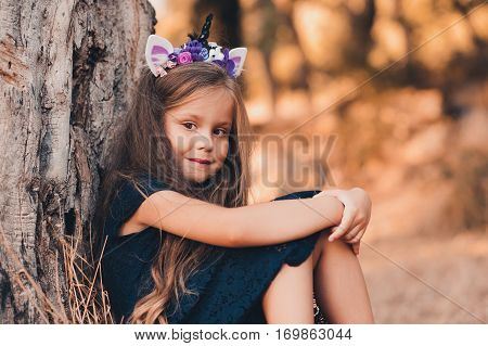 Smiling kid girl 5-6 year old wearing unicorn headband and black dress sitting under tree in park. Looking at camera. Childhood.