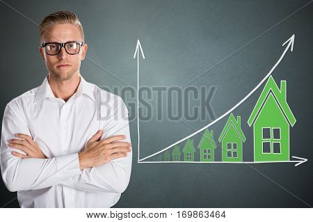 Young Confident Businessman With Real Estate Concept Over Grey Background