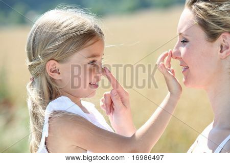 Mother and daughter putting sunscreen on their face