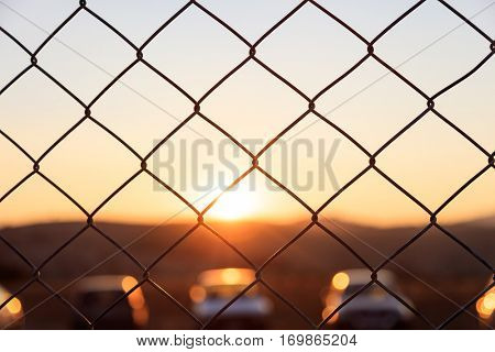 Steel wire mesh fence on a sunset background